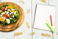 Banta på planet - en sallad av nya grönsaker och en tom anteckningsbok Arkivbilder