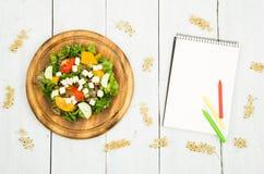 Banta på planet - en sallad av nya grönsaker och en tom anteckningsbok Arkivfoton