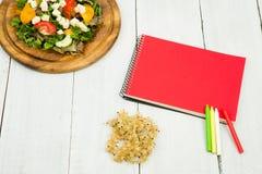Banta på planet - en sallad av nya grönsaker och en tom anteckningsbok Royaltyfri Fotografi