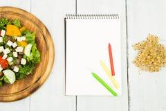 Banta på planet - en sallad av nya grönsaker och en tom anteckningsbok Arkivfoto