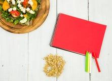 Banta på planet - en sallad av nya grönsaker och en tom anteckningsbok Royaltyfri Bild