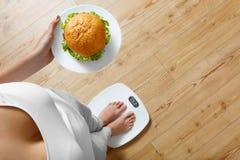 Banta snabbmat Överviktig kvinna på skalan, hamburgare Skräpmat royaltyfri foto