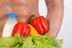 banta sporten Attraktiv man med den muskulösa kroppen Idrotts- grabb och grönsaker royaltyfria bilder
