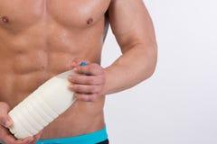 banta sporten Attraktiv man med den muskulösa kroppen Den idrotts- grabben och flaskan av mjölkar arkivfoton