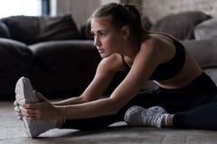 Banta sportigt Caucasian flickasammanträde på golvet som gör sträcka övning inomhus fotografering för bildbyråer