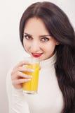 banta Sund livsstil En ung flicka som dricker ny orange fruktsaft Vit bakgrund Arkivbild