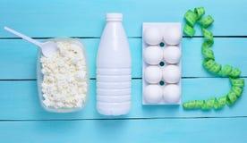 Banta sund mat Flaska av yoghurten, keso, äggmagasin på en blå träbakgrund Linjal för midjamätning fotografering för bildbyråer