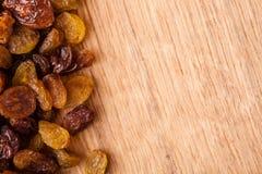 Banta sund mat. Gräns av russinet på träbakgrund Royaltyfri Bild