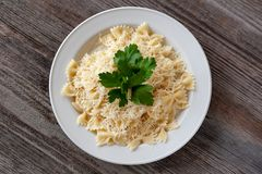 banta sunt Farfalle pasta med ost på en vit platta, dekor royaltyfria bilder