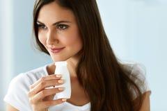 banta sunt Härlig le kvinna som dricker naturlig yoghurt royaltyfria foton