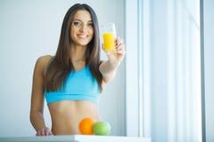 banta Ung attraktiv lycklig kvinna med exponeringsglas av fruktsaft arkivfoto