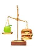 Banta valet mellan äpplet och hamburgaren royaltyfria bilder