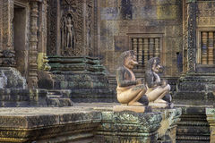 Bantaey Srei guardians. Two kneeling monkey statues before intricately carved pink sandstone temple walls royalty free stock photo