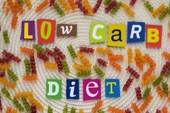 Bantar den låga carben för inskriften från mångfärgade bokstäver som visar äta sunt begrepp Ett ord som skriver text som, den låg royaltyfri fotografi