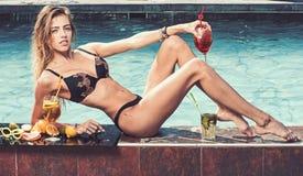 Bantar ny vitaminfruktsaft för drinken, Modekvinnan med förnyar alkohol i miami Sommarsemester och simning på havet pöl royaltyfri foto