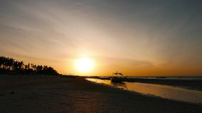 Bantayan sunrise. A Bantayan Island sunrise video, with a local boat grounded because of the low tide, and birds feeding on small shells and fish trapped in the stock video footage