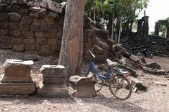 Banteay Top temple, grounds with bike propped near tree. Banteay Top or Fortress of the Army, is a small temple with tall, damaged towers. Believed to be a Stock Images