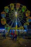 BANYUWANGI, ИНДОНЕЗИЯ: Играть увиденный Locals вокруг перед малым колесом ferris, обнаруженным местонахождение внутренним очарова Стоковая Фотография RF