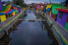 BANYUWANGI, INDONESIË: Waterkanaal van brug met kleurrijke huizen aan beide kanten wordt gezien, charmante bewolkte die buurt, Royalty-vrije Stock Foto