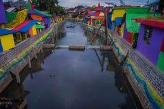 BANYUWANGI, INDONESIË: Waterkanaal van brug met kleurrijke huizen aan beide kanten wordt gezien, charmante bewolkte die buurt, stock afbeeldingen