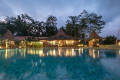 Banyuwangi, Indonesia - Architecture wooden resort bali style with swimming pool and illumination in dusk. At Ijen island royalty free stock images