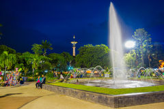 BANYUWANGI, INDONESIA: Charming park area with green vegetation and popular water fountain, people enjoying, beautiful. Blue evening sky in background Royalty Free Stock Images