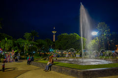 BANYUWANGI, INDONESIA: Charming park area with green vegetation and popular water fountain, people enjoying, beautiful. Blue evening sky in background Royalty Free Stock Image