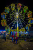BANYUWANGI, INDONESIA: Locals seen playing around in front of small ferris wheel, located inside charming park area. Night sky background Royalty Free Stock Photography