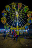 BANYUWANGI, INDONESIA: Locals seen playing around in front of small ferris wheel, located inside charming park area. Night sky background Stock Image
