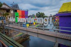 BANYUWANGI, INDONESIEN: Wasserkanal gesehen von der Brücke mit bunten Häusern auf beiden Seiten, reizend Nachbarschaft, bewölkt lizenzfreie stockbilder
