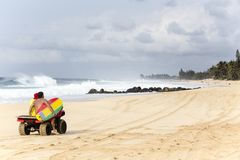Banzai Pipeline of Northshore, Oahu. A surfer riding behind an ATV, holding a surfboard  with barrels of Banzai Pipeline at the background Royalty Free Stock Photos