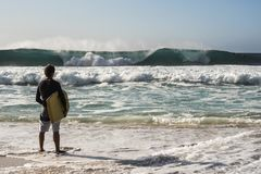 Young surfer is watching other people surfing big waves royalty free stock photo