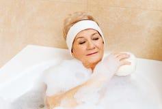 Baño de la mujer que se relaja con la esponja Fotos de archivo