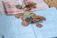 Baño del dinero y libreta de banco de cuenta tailandeses de ahorro Imagen de archivo