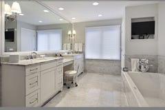 Baño principal con el cabinetry blanco Imagenes de archivo