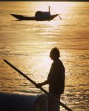 Baotman on Ganges. Sparkling water silhouette of oars man royalty free stock photo