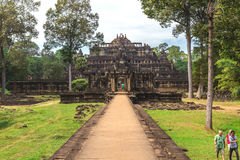 Baphuon: Tower and galleries and walking tourists Stock Images