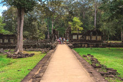 Baphuon: Tower and galleries and walking tourists Stock Photo