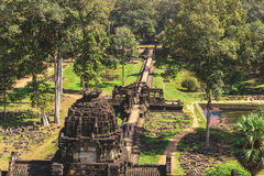 Baphuon: Tower and galleries and walking tourists. Angkor Thom, Baphuon Temple, Siem Reap, Cambodia - December 7, 2016: Tower and galleries and walking tourists Stock Photography
