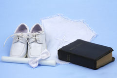 Baptism. Religious baptism items, candle, shoes, bow tie, and bible on blue background royalty free stock photo