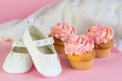 Baptism or birthday girl invitation with pink cup cakes and whit. E shoes on pink background stock photo