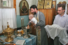 Baptism of the child in the Orthodox Church. The young Orthodox priest keeps the baby over a bowl of holy water in the Church. Nearby is the godfather of the Stock Image