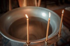 Baptismal font, orthodox church, three candles stock images