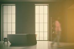 Baquet blanc dans une salle de bains grise avec la tache floue blanche de plancher Photographie stock libre de droits