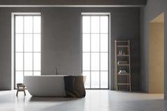 Baquet blanc dans une salle de bains grise avec le plancher blanc Image stock