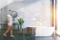 Baquet et évier blancs dans une salle de bains de grenier, femme Photo stock