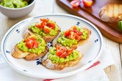 Crostini com abacate e tomate imagens de stock