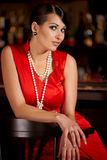 In the bar. Glamorous brunette woman in pearl beads in bar Royalty Free Stock Photos