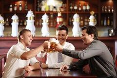 In the bar. Three young men bob mugs in the bar Stock Photo