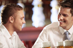 At the bar. Two young men with a beer in a bar Royalty Free Stock Images